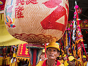 """23 JUNE 2015 - MAHACHAI, SAMUT SAKHON, THAILAND: An attendant carries a Chinese lantern in the City Pillar Shrine Procession in Mahachai. The Chaopho Lak Mueang Procession (City Pillar Shrine Procession) is a religious festival that takes place in June in front of city hall in Mahachai. The """"Chaopho Lak Mueang"""" is  placed on a fishing boat and taken across the Tha Chin River from Talat Maha Chai to Tha Chalom in the area of Wat Suwannaram and then paraded through the community before returning to the temple in Mahachai.   PHOTO BY JACK KURTZ"""