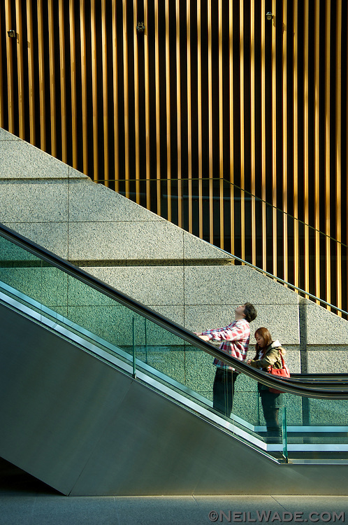 A man and woman ride an escalator in Tokyo, Japan.