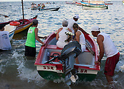 Mother and daughter on a boat into the sea to make their offerings to Yemenja. February 2nd is the feast of Yemanja, a Candomble Umbanda religious celebration, where thousands of adherants visit the Rio Vermehlo Red River to make offerings of flowers and prayers, paying their respects to Yemanja, the Orixa goddess of the Sea and water.