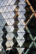 Façade of 30 St Mary Axe, also known as the Gherkin, at dusk. The double façade creates a natural ventilation system and giant double glazing effect; air is sandwiched between two layers of glazing and insulates the office space inside. The triangulated perimeter structure is structural and adds to the buildings rigidity. Architect Foster + Partners (2004). Engineer: Arup. London, UK, 2009