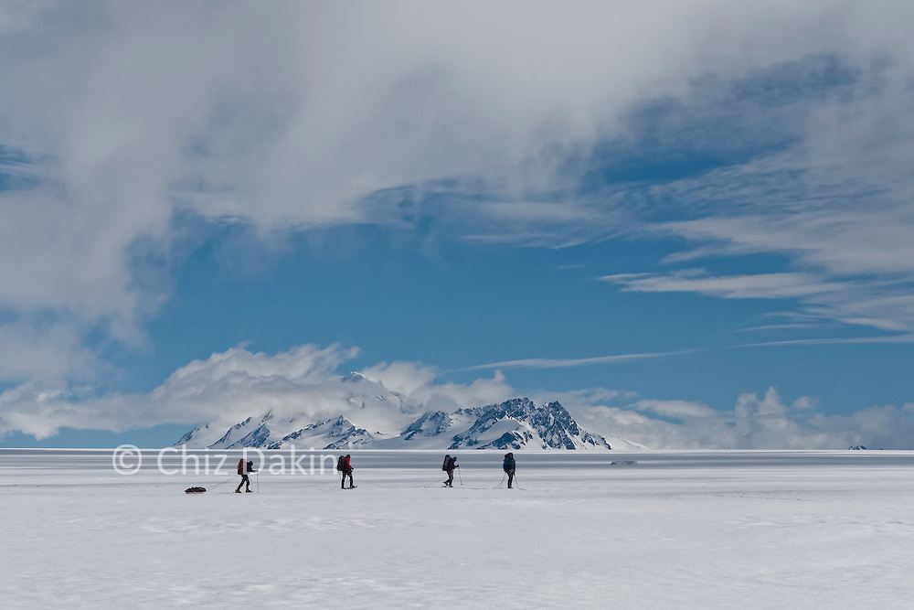 Team roped up on the ice cap with pulka at the back of the rope - Nunatak Viedma in the background
