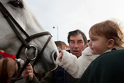 © Licensed to London News Pictures. 26/12/2012. Tenterden, Kent. Alice Chapple, 17 months, granddaughter of the Whip of the hunt greets Mac the horse as the townsfolk of Tenterden gather for the Ashford Valley Hunt meet and greet on Boxing Day. Photo credit : Rebecca Mckevitt/LNP