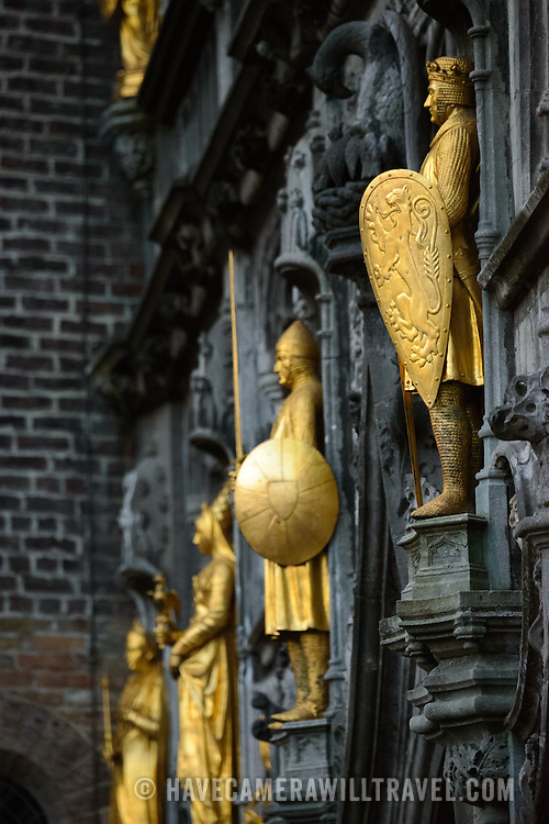 Gold statues on the exterior of the Basilica of the Holy Blood on Burg Square in central Bruges, Belgium.