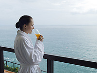 beautiful calm and serene woman in palace hotel room at the balcony facing the sea driking orange juice