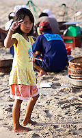 Young girl giving a peace sign with her fingers on China Beach, Vietnam.