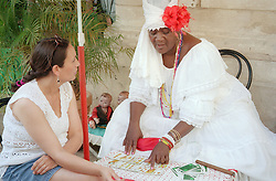 Practitioner of the Santeria religion with tarot style cards and client in Havana; Cuba,