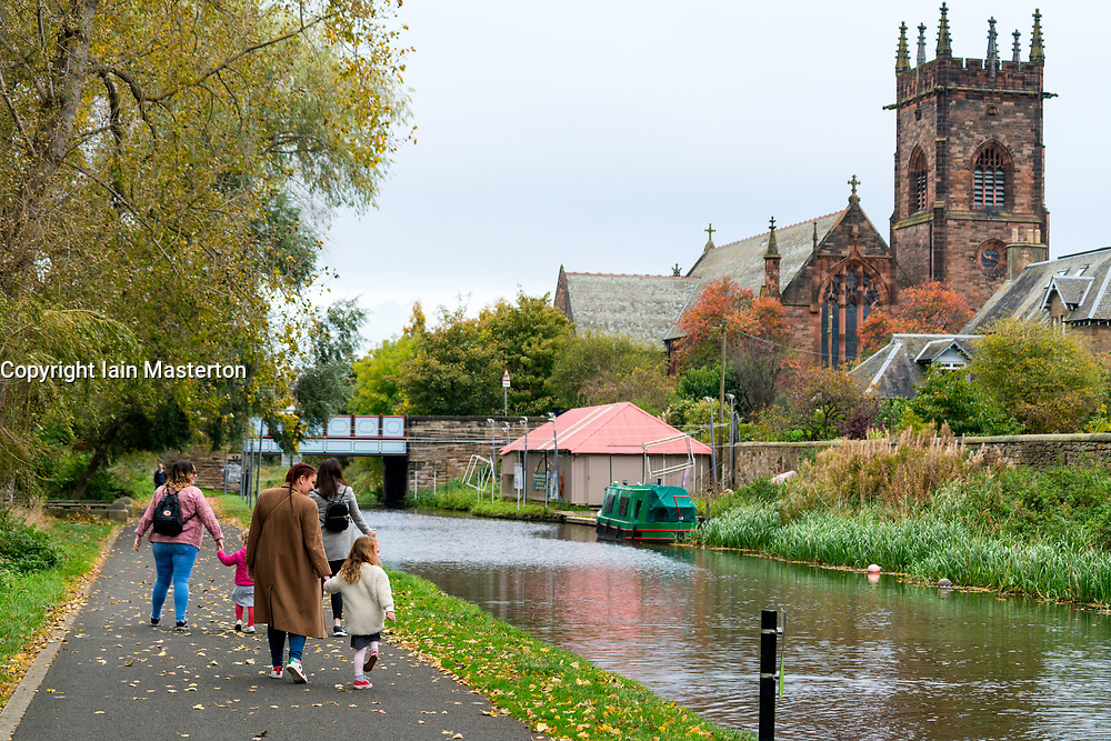 Family walking along towpath beside the Union Canal at Polwarth in Edinburgh, Scotland, United Kingdom.