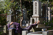 A homeless man sleeps on gravestones in a cemetery in Azabu, Tokyo, Japan. Friday February 17th 2017