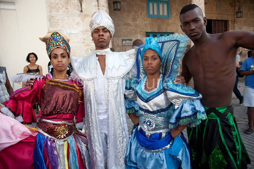 Male and female Cubans of African and mixed descendancy posing for a portrait wearing colourful costumes, performance in Havana old town, local dance and theatre group enacting the slave trade, colonial rule and how African religion and beliefs continuing, becoming what is now Santeria.