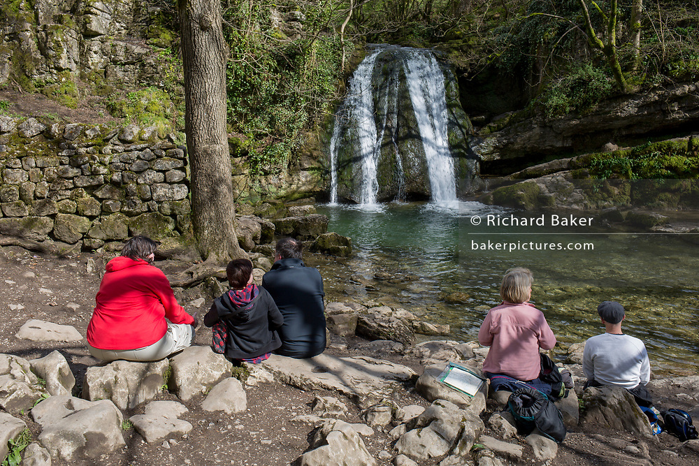 Walkers sit and picnic on rocks, admiring the Yorkshire Dales waterfall called Janet's Foss on 12th April 2017, in Malham, Yorkshire, England. Janet's Foss is a small waterfall in the vicinity of the village of Malham, North Yorkshire, England. It carries Gordale Beck over a limestone outcrop topped by tufa into a deep pool below. The pool was traditionally used for sheep dipping, an event which took on a carnival air and drew the village inhabitants for the social occasion. The name Janet (sometimes Jennet) is believed to refer to a fairy queen held to inhabit a cave at the rear of the fall. A foss is an old Norse word meaning waterfall.