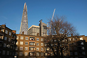 The Shard towering over a council housing estate in Southwark, London, UK. The Shard, also referred to as the Shard of Glass, Shard London Bridge and formerly London Bridge Tower, is an 87-storey skyscraper in London that forms part of the London Bridge Quarter development.