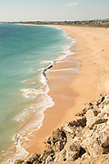 View of sea and sandy beach with buildings in background, Cadiz, Andalusia, Spain