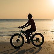 Silhouette of a man on a bike on Cenang beach, Langkawi, Malaysia at sunset