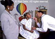 Doctor, Physician at Work, African American Physician and Black Child Patient, Mother Watches