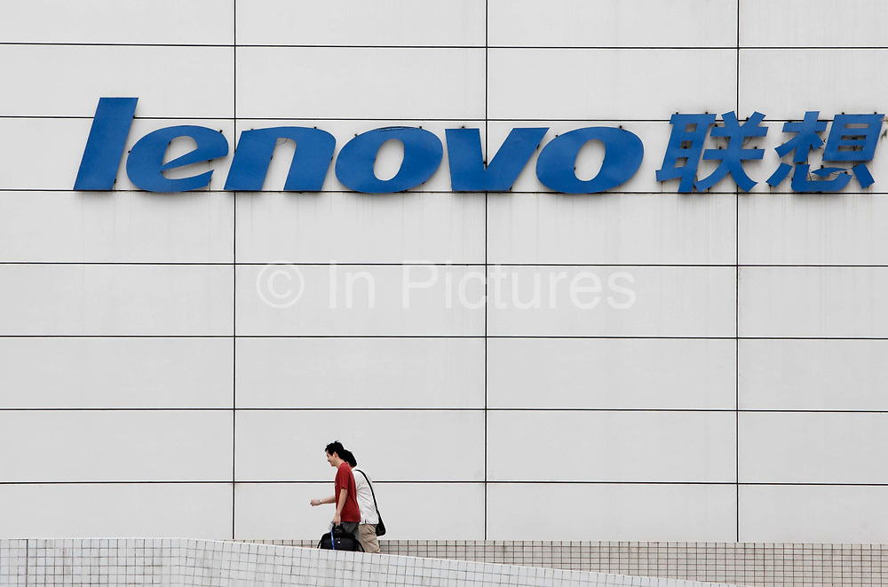 Pedestrians walk past the Lenovo regional head quarters in Shanghai, China on 04 August 2009.  Lenovo is currently the 4th largest personal computer vendor in the world, in 2005 it bought IBM's personal computer division for USD 1.75 billion.