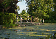 A view over the moat to a seating area in the formal garden at Hindringham Hall, Hindringham, Norfolk, UK