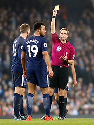 Referee Craig Pawson shows a yellow card to Tottenham Hotspur's Mousa Dembele