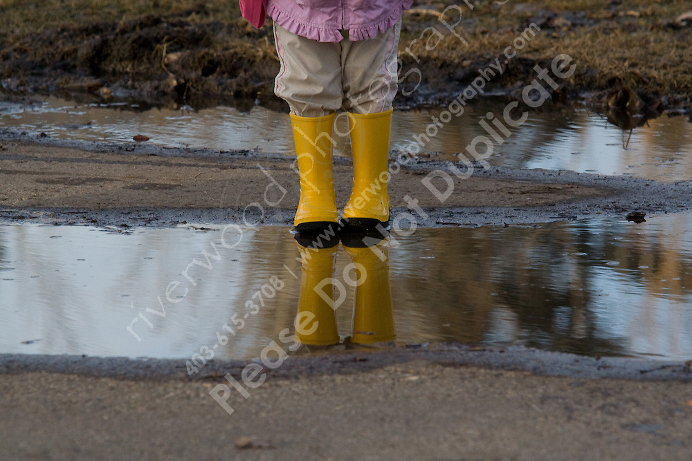 These boots are made for...<br /> <br /> A child with yellow boots steps into a puddle and the boots are reflected back off the water.