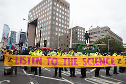 Environmental activists from Extinction Rebellion hold a banner in front of a vintage bus used to block a road junction to the south of London Bridge on the ninth day of their Impossible Rebellion protests on 31st August 2021 in London, United Kingdom. Extinction Rebellion are calling on the UK government to cease all new fossil fuel investment with immediate effect.