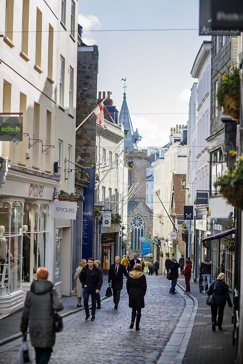 People shopping and walking along the pedestrianised retail high street in the centre of town in Guernsey, Channel Islands