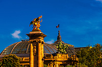 Gilded sculptures featuring winged horses of the Pont Alexandre III (bridge) with the Grand Palais in background, Paris, France.