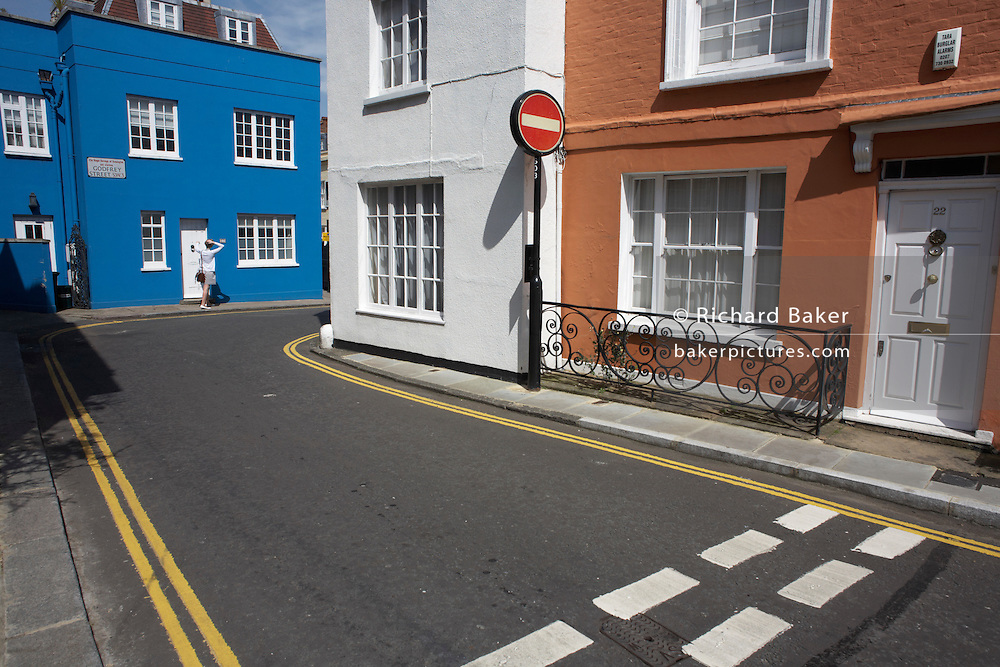 Single pedestrian is about to enter a property in the quiet one-way Godfrey Street off King's Road, Chelsea, SW3