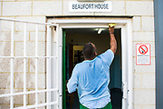 A wing cleaner wipes down the door frame of Beaufort House, a skill development unit for enhanced prisoners. Part of HMP/YOI Portland, a resettlement prison with a capacity for 530 prisoners.Dorset, United Kingdom.