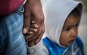Always being a protective father, Rosalino holds onto Josue's hand as they wait for a car to pass outside of their home in Santa Ana. Nick Wagner / Alexia Foundation