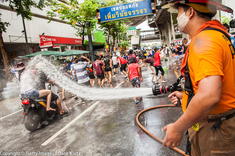 14 APRIL 2013 - BANGKOK, THAILAND:  A firefighter hoses down the crowd in a community water fight on April 14, 2013 in Bangkok, Thailand. The Songkran festival is celebrated in Thailand as the traditional New Year's Day from 13 to 15 April. The throwing of water originated as a way to pay respect to people and is meant as a symbol of washing all of the bad away. PHOTO BY JACK KURTZ
