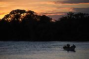 A family fishes at sunset over the San Juan River. Boca de Sábalos, El Castillo, Río San Juan, Nicaragua. January 26, 2014.