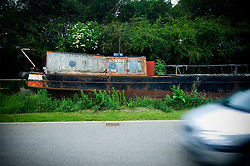 Old canal boat on dry land by the roadside near Foxton Locks on the Grand Union Canal, Market Harborough, Leicestershire, England, UK.