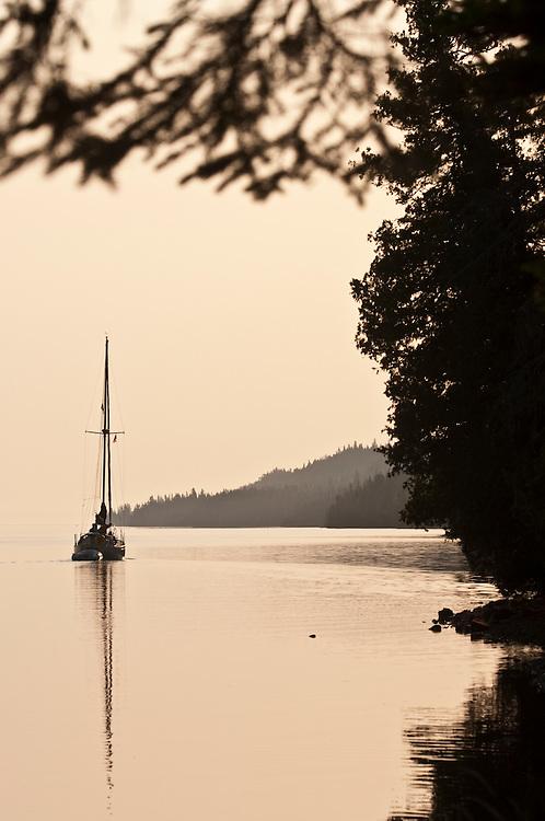 A sailboat motors through Duncan Bay on Lake Superior at Isle Royale National Park.