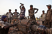 A group of men and teenage boys break up an armature to reclaim the copper. The armature is an electrical engine component from a ship.  They work in an internationally renowned marine breaking scrap yard just outside Bhavnagar, Gujarati. Lots of children work at the yard and the Shaishav Trust is trying to provide education and support for children in child labour.