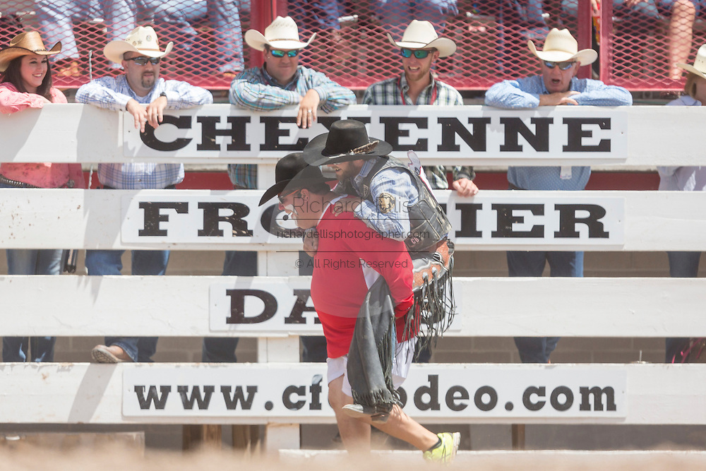 A rodeo clown carries Saddle Bronc rider Wade Sundell on his back at the Cheyenne Frontier Days rodeo at Frontier Park Arena July 24, 2015 in Cheyenne, Wyoming. Frontier Days celebrates the cowboy traditions of the west with a rodeo, parade and fair.