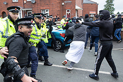 © Licensed to London News Pictures . 18/05/2019. Oldham, UK. Police push back those opposed to Yaxley-Lennon after bottles, bricks and eggs are thrown by both sides at each other and fights break out . Former EDL leader Stephen Yaxley-Lennon (aka Tommy Robinson ) continues his campaign for a seat in the European Parliament representing the North West of England , by visiting Oldham . Photo credit: Joel Goodman/LNP