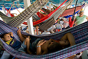 Riverboat passengers relax in a web of hammocks on the Solimoes River upstream from Manacapuru, Brazil.