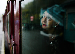© Licensed to London News Pictures. <br /> 15/10/2016. <br /> Grosmont, UK.  <br /> <br /> A wonan in period clothing looks out of a train window at Grosmont station during the North Yorkshire Moors Railway Wartime Weekend event. <br /> The annual event brings together re-enactors and enthusiasts along the length of the NYMR heritage steam railway line to recreate the feel of the war years of the 1940's. <br /> <br /> Photo credit: Ian Forsyth/LNP