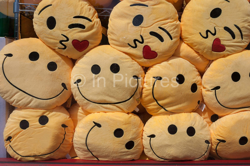 A detail display of heaps of smiley face happiness cushions which are piled up in the window of a general store shop in Brixton, south London borough of Lambeth, England on 6th June 2016.