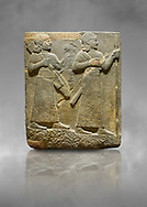 Hittite relief sculpted orthostat stone panel of Royal Buttress. Basalt, Karkamıs, (Kargamıs), Carchemish (Karkemish), 900-700 B C. Warriors. Anatolian Civilisations Museum, Ankara, Turkey.<br /> <br /> Two figures are seen, each with a long dress, a thick belt and curled hair. The figure in front carries a spear in his left hand and a long sword at his waist, and the figure behind carries an axe in his left hand and a quiver on his back.   <br /> <br /> Against a grey art background. .<br />  <br /> If you prefer to buy from our ALAMY STOCK LIBRARY page at https://www.alamy.com/portfolio/paul-williams-funkystock/hittite-art-antiquities.html  - Type  Karkamıs in LOWER SEARCH WITHIN GALLERY box. Refine search by adding background colour, place, museum etc.<br /> <br /> Visit our HITTITE PHOTO COLLECTIONS for more photos to download or buy as wall art prints https://funkystock.photoshelter.com/gallery-collection/The-Hittites-Art-Artefacts-Antiquities-Historic-Sites-Pictures-Images-of/C0000NUBSMhSc3Oo