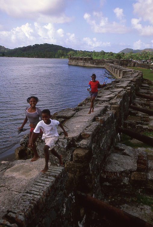 Local children playing along historic wall at World Heritage Site the Fort of Santiago in Portobelo, Panama, CA.