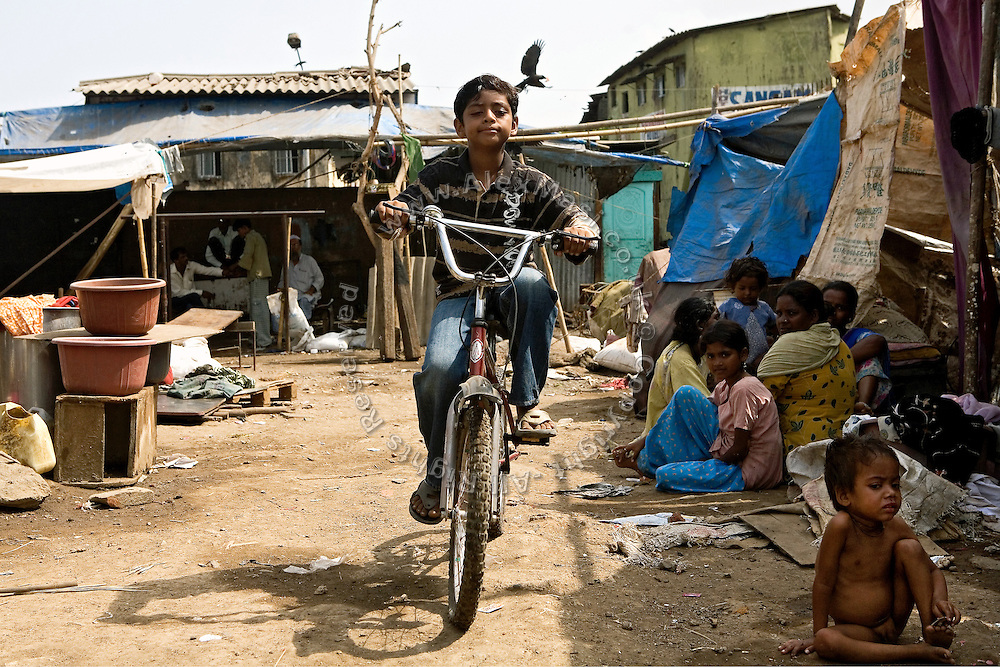 Azharuddin Ismail, 10, the child actor playing the role of 'young Salim', the brother of Jamal, protagonist of Slumdog Millionaire, the famous movie winner of 8 Oscar Academy Awards in December 2008, is riding his bicycle in the slum where he still lives with his family next to the train station of Bandra (East), Mumbai, India. Various promises were made to lift the two young actors (Azharuddin Ismail and Rubina Ali) from poverty and slum-life but as of the end of May 2009 anything is yet to happen. Rubina's house was recently demolished with no notice as it lay on land owned by the Maharashtra train authorities and she is now permanently living with her uncle's family in a home a stone-throw away in the same slum. Azharuddin's home too was demolished in the past two weeks, as it happens every year in his case, because the concrete walls were preventing local authorities to clear a drain passing right behind it. As usual, his father is looking into restoring the walls as soon as the work on the drain has been completed.