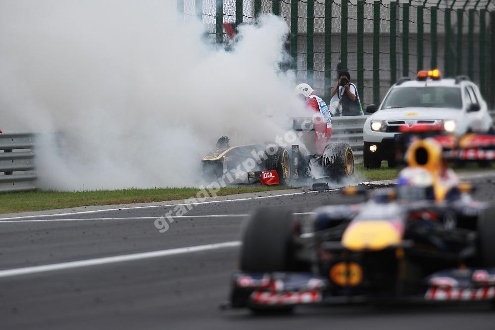 The Lotus-Renault of Nick Heidfeld on fire while Sebastian Vettel (Red Bull-Renault) passes in the 2011 Hungarian Grand Prix at the Hungaroring. Photo: Grand Prix Photo