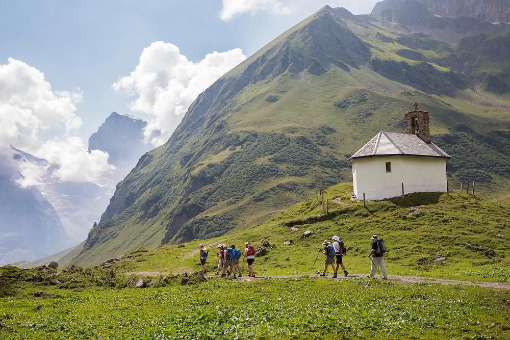Hikers passing chapel on the Via Alpina, Swiss Alps