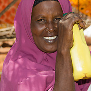 Delighted recipient of cooking oil during the East African drought. Wajir, North Eastern Province, Kenya.