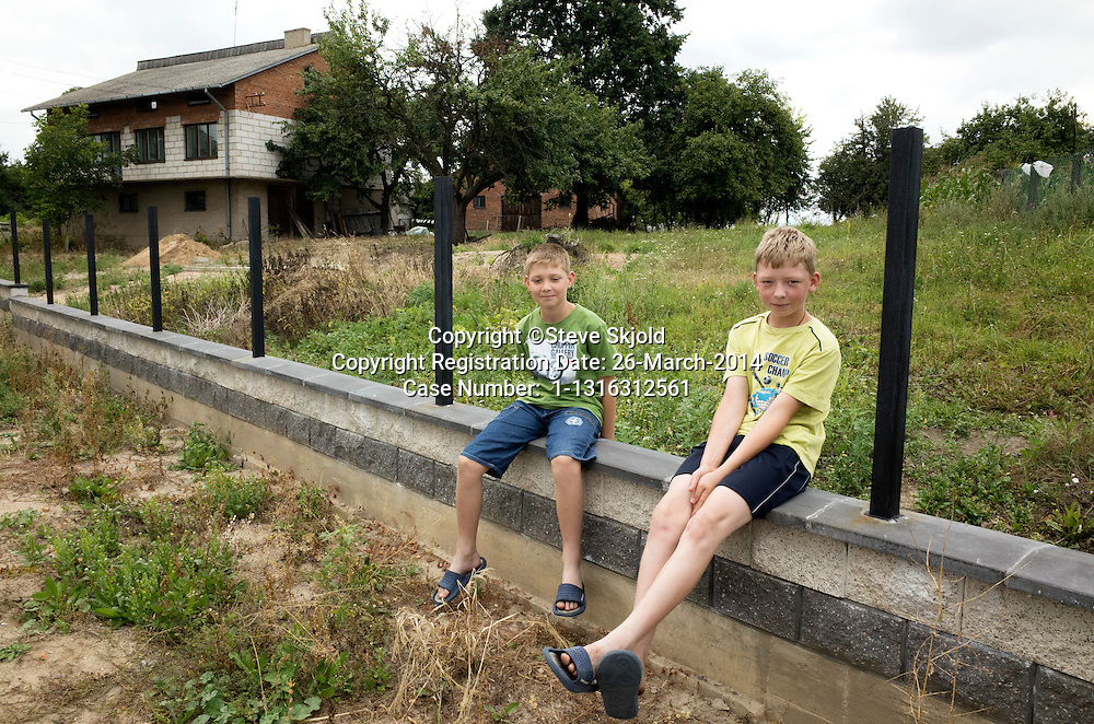 Polish boys age 10 and 11 providing friendly commentary on bicyclers passing by on country road. Rzeczyca Central Poland