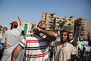 A Morsi supporter makes a throat cutting guesture in reference to General Sisi, head of the military that have taken over control of the country, since arresting Mohammed Morsi.