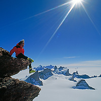 Conrad Anker relaxes near the summit of Mount Kubus with the Filchner Mountains in the background, Queen Maud Land, Antarctica.