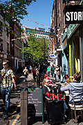 Friends sitting outside a cafe in the Spring sunshine on Neal Street in Covent Garden, London.