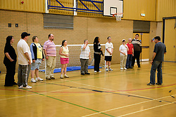 Group of Day Service users with learning disabilities lining up and listening to a Care Assistant giving instruction before an indoor sports game in the gym,