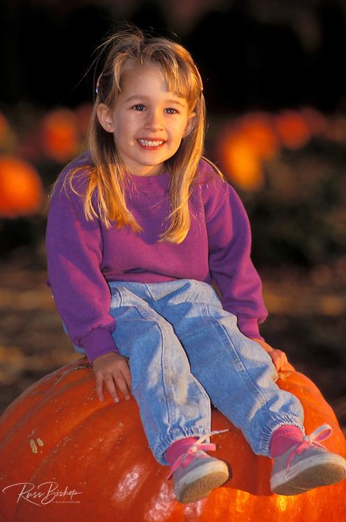 Child (age 3) sitting on a giant pumpkin at the Faulkner Farm, Santa Paula, California
